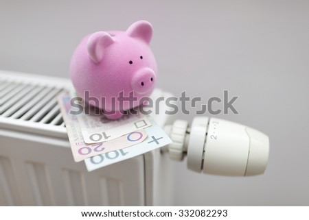 Piggy bank with polish money on radiator. Energy saving concept.  - stock photo