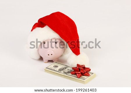 Piggy bank with Santa Claus hat and stack of money american hundred dollar bills with red bow standing  on white background - stock photo