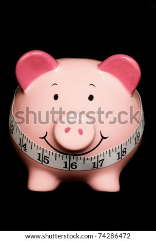 Piggy bank with tape measure isolated on black - stock photo