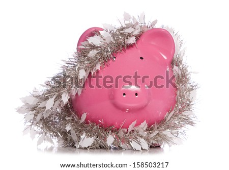 Piggy bank wrapped in Christmas tinsel studio cutout - stock photo