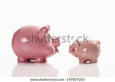 Piggy banks, opposing each other - stock photo