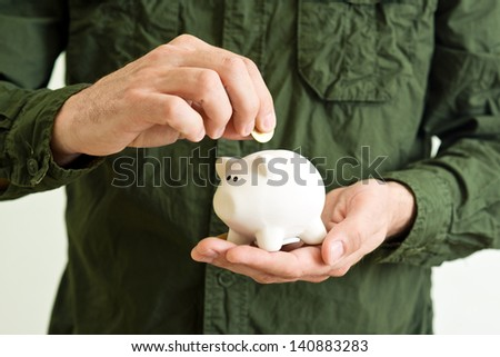 Piggy coin bank in cupped hands of man. - stock photo
