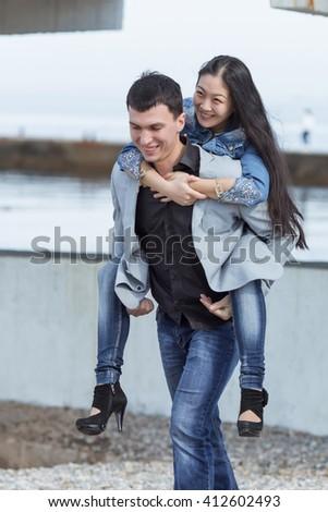 Piggyback. European guy carrying on shoulders his asian girl - stock photo