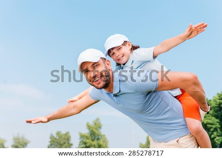 Piggyback ride. Smiling young man piggybacking his son while standing outdoors - stock photo