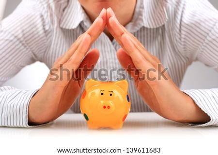 Piggybank and hands. - stock photo