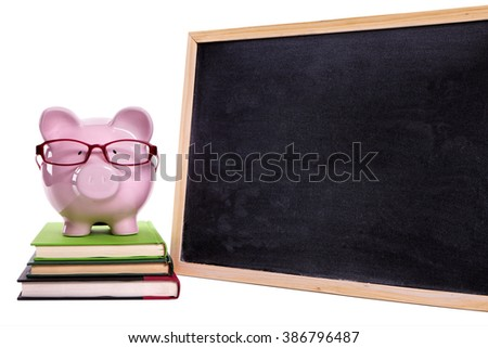 Piggybank wearing glasses on small stack of books, blank blackboard, college education success concept - stock photo