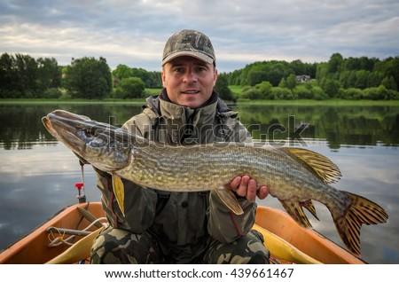 Pike fishing in summer Scandinavian lake - stock photo