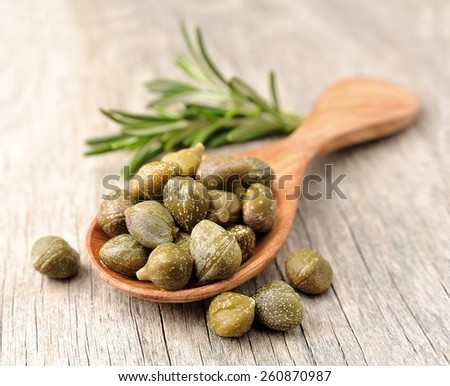 Pikled capers on wooden texture. - stock photo