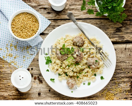 Pilaf of bulgur with meat balls on old wooden table, dining meal in oriental style top view - stock photo