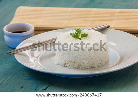 pilaf rice on white plate with two chopstick and soy sauce - stock photo