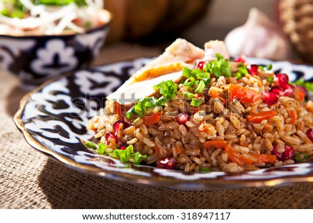 Pilaf - Rice with Chicken, Vegetables and Pomegranate. Garnished with Onions and Tomatoes Salad - stock photo