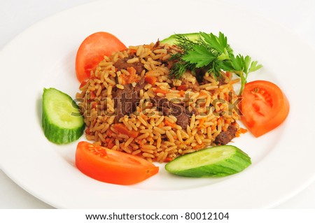 Pilaf with vegetables on a white plate - stock photo