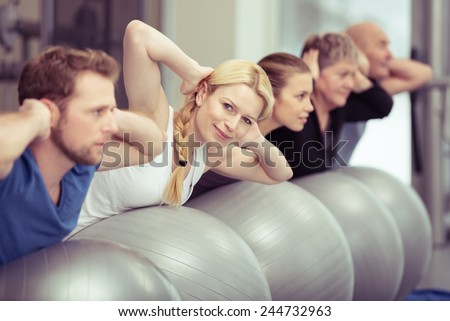 Pilates class at a gym with diverse people in a receding row exercising with their gym balls, young and elderly, men and women, with focus to an attractive blond woman - stock photo