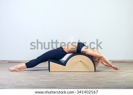Pilates, fitness, sport, training and people concept -  woman doing  exercises on small barrel. - stock photo