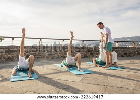 Pilates personal trainer in a group class outdoors - stock photo