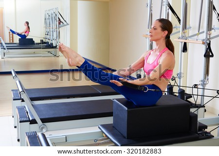 Pilates reformer woman short box teaser exercise workout at gym indoor - stock photo