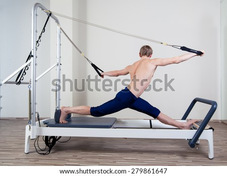 Pilates reformer workout exercises man at gym indoor - stock photo