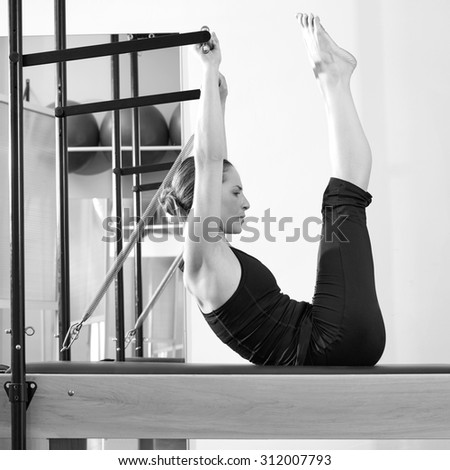 Pilates woman in reformer exercise at gym indoor - stock photo