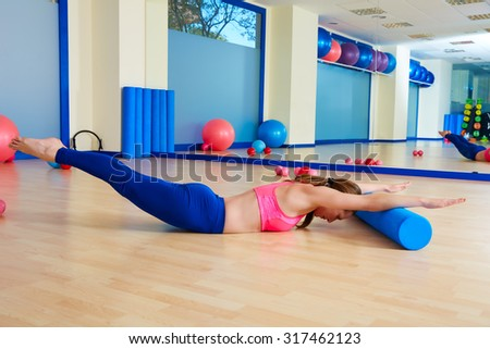 Pilates woman roller swan dive roll exercise workout at gym indoor - stock photo