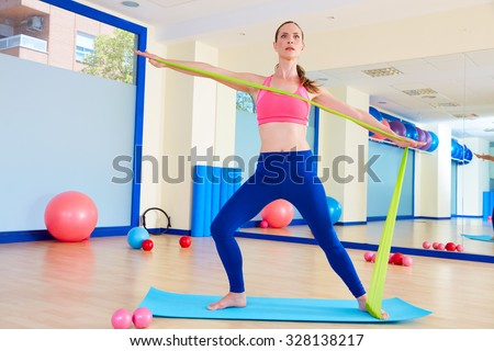 Pilates woman standing rubber band exercise workout at gym indoor - stock photo