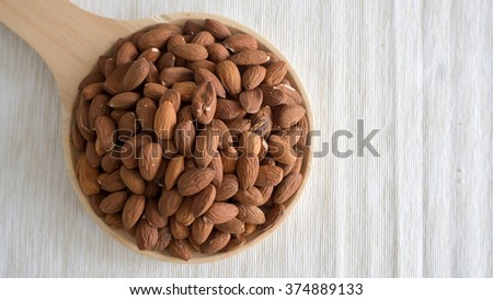 Pile of almonds on wooden plate. - stock photo