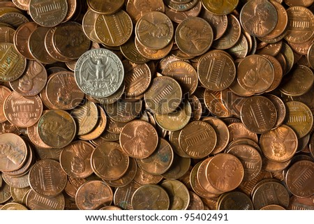 Pile of American Pennies with a Quarter of Dollar coin on it. - stock photo