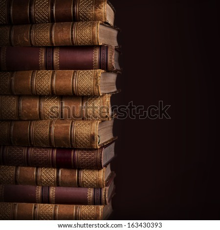 Pile of ancient books on brown background - stock photo