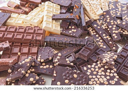 pile of assorted chocolate bars - heap of black and white chocolate pieces with hazelnuts  - stock photo