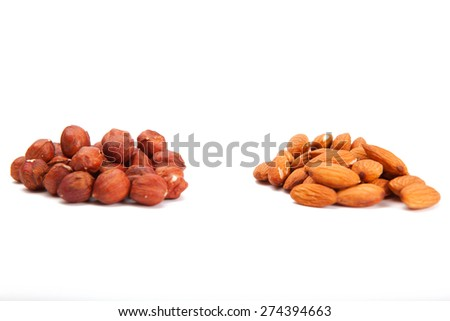 Pile of assorted nuts on white. Heap hazelnut and almonds  on a white background. - stock photo