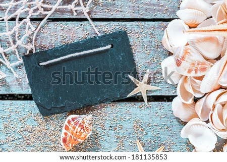Pile of assorted seashells with a blank retro school slate with copyspace on rustic wooden table with scattered beach sand, fishing net and starfish - stock photo