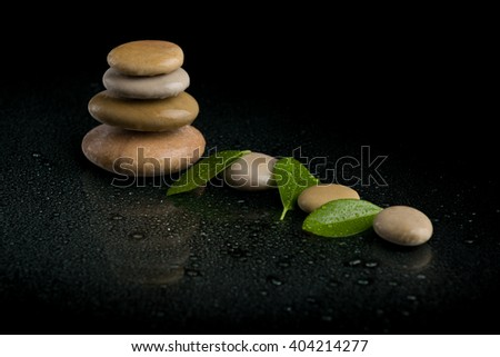 Pile of balancing pebble stones and green leaf with eater drop, ZEN stone, on black background, spa tranquil scene concept with reflection - stock photo