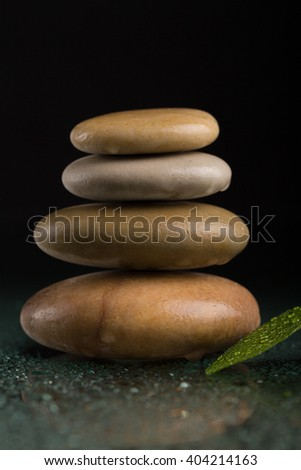 Pile of balancing pebble stones and green leaf with water drop, ZEN stone, on black background, spa tranquil scene concept with reflection - stock photo