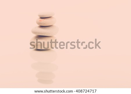 Pile of balancing pebble stones, like ZEN stone, isolated on white background, spa tranquil scene concept with reflection, retro color pastel tone - stock photo