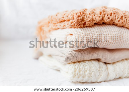 Pile of beige woolen clothes on a white background. Warm knitted sweaters and scarfs are folded in one heap - stock photo