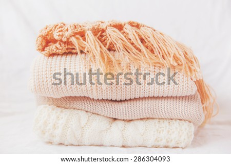 Pile of beige woolen clothes on a white background. Warm knitted sweaters and scarfs are folded in one heap. Imitation of Instagram style tone. - stock photo
