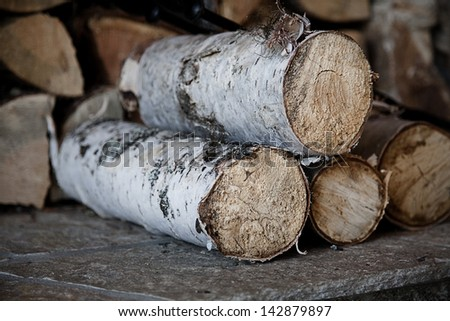 Pile of birch wood by the fireplace - stock photo