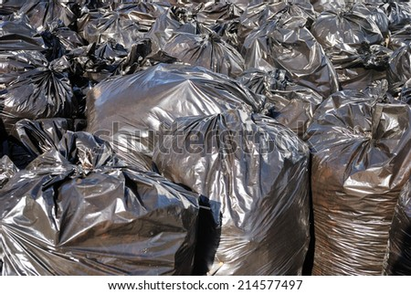 pile of black garbage bags with tons of trash - stock photo
