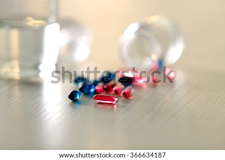 Pile of blue and red capsules with glass of water on the table, close up - stock photo