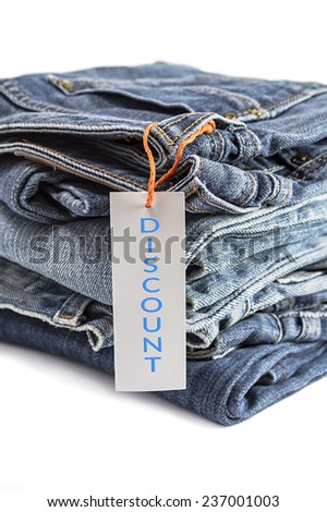 Pile of blue jeans with label isolated on white background. Selective focus on tag label. - stock photo