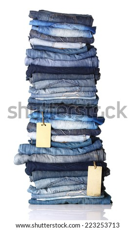 Pile of blue jeans with tags isolated on white. - stock photo