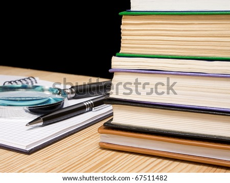 pile of book and pen on notebook on black background - stock photo
