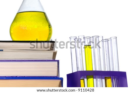 pile of books and some retorts with yellow liquid, isolated on white - stock photo