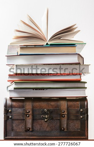 Pile of books costs on an old chest. - stock photo