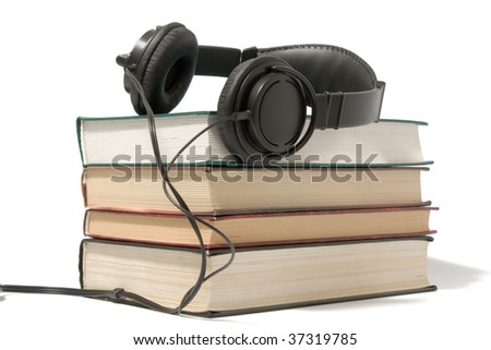 Pile of books in headphones, can illustrate the audiobooks concept. Isolated on white. - stock photo