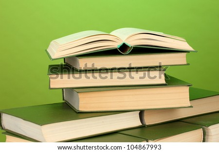 pile of books on green background close-up - stock photo