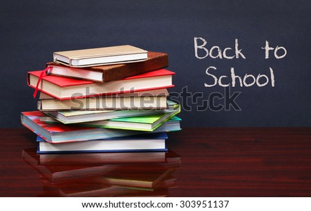 Pile of books on the desk. The words 'Back to School' written in chalk on the blackboard - stock photo