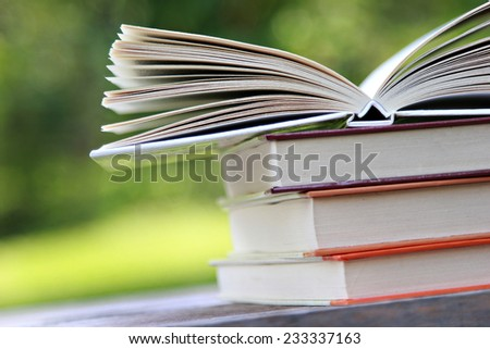 Pile of books on the table with open ones - stock photo