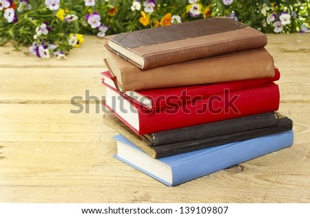 Pile of books on wooden vintage table, fresh blooming flowers in the background. - stock photo
