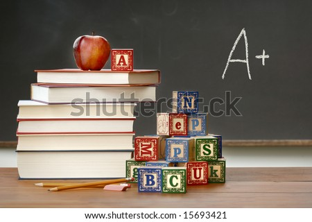 Pile of books with wooden blocks in front of chalkboard - stock photo