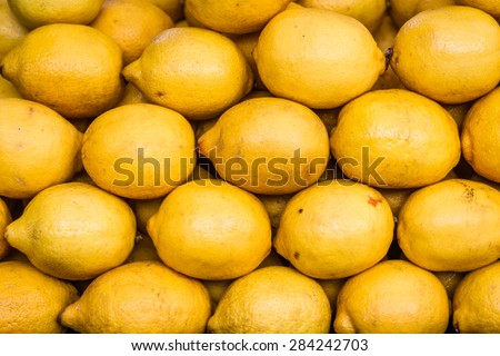 Pile of bright yellow lemons in fruit market, lemon background - stock photo